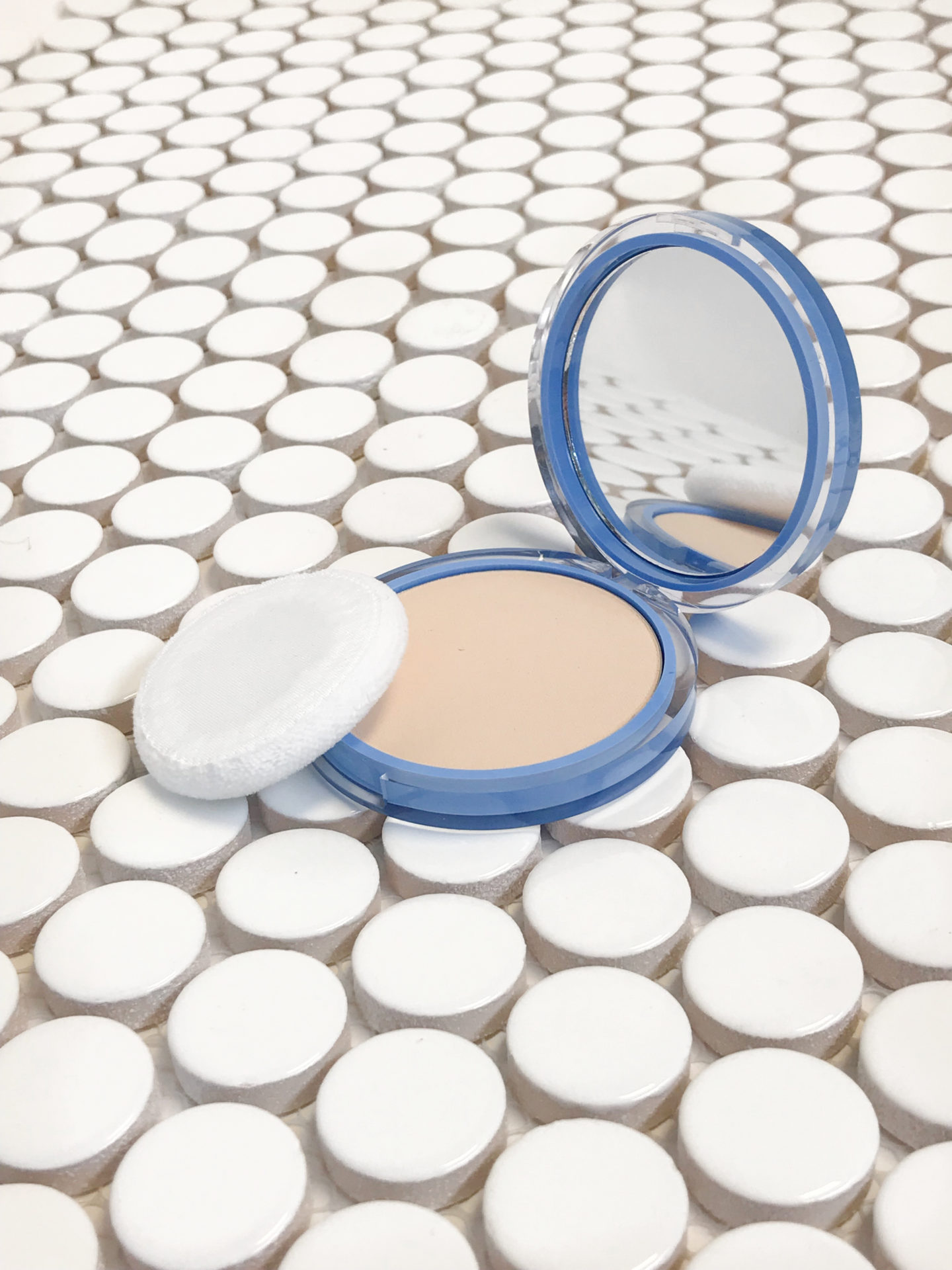 Pressed Powder Compact on White Tile