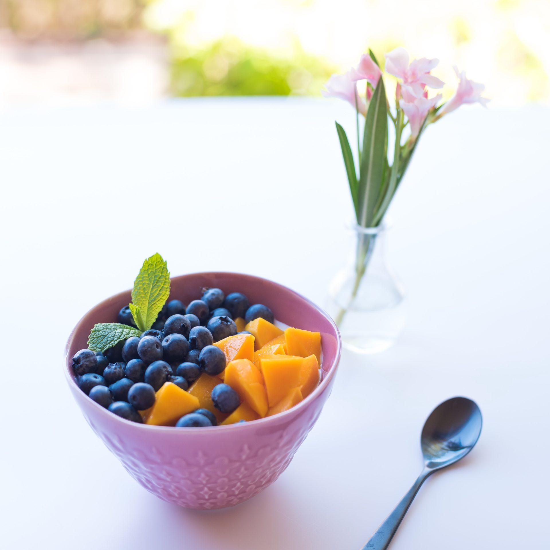 Fruit and Yogurt Bowl with spoon and flower