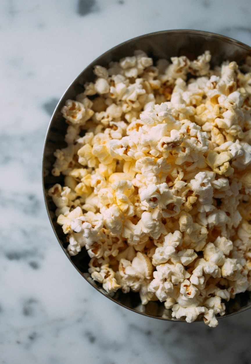 Popcorn in dark bowl on marble counter